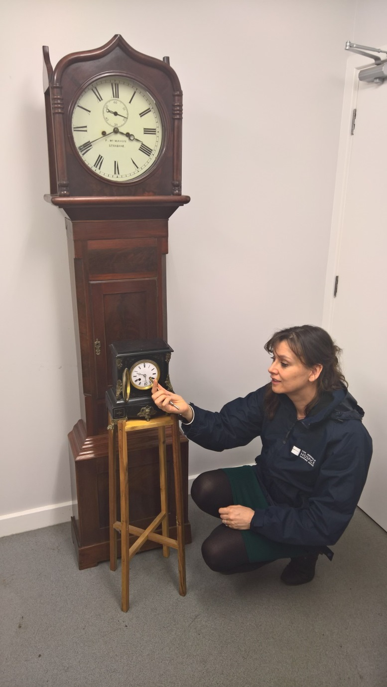 A grandfather clock and table clock with a  femail member of the Hospice retail team
