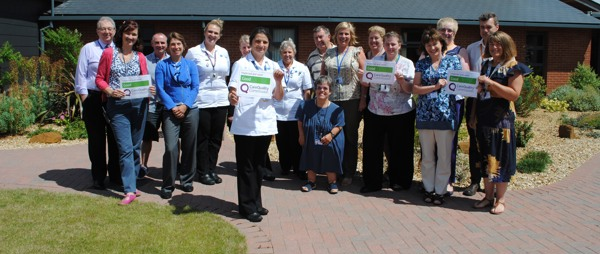 A group of Hospice staff and volunteers outside holding Good signs