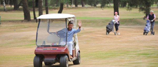 Man in golf buggy and two golfers walking