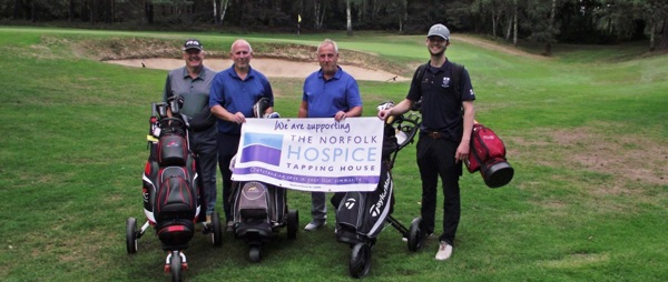 four golfers with hospice banner