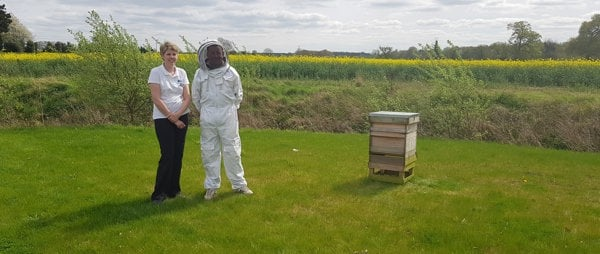 Emma and beekeeper with beehive