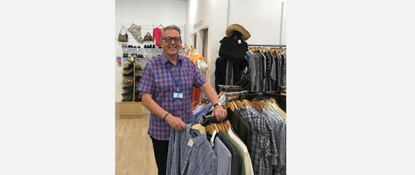 Retail volunteer beside a clothing rail