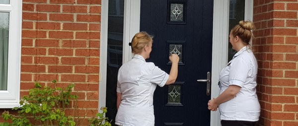 two nurses knocking on a door