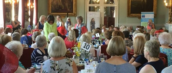 A room full of ladies enjoying a fashion show