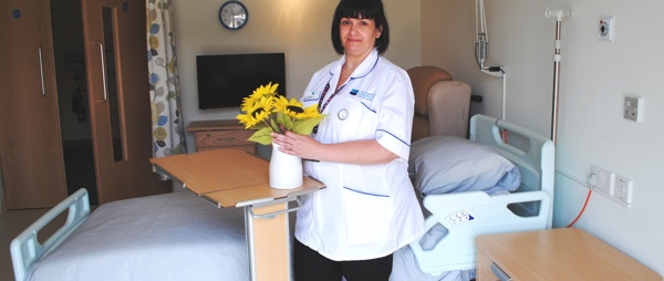 A nurse arranging flowers on a table next to a bed