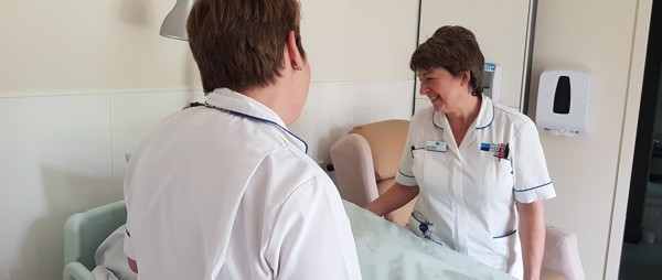 two nurses talking to a patient
