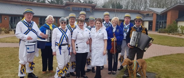 a group of morris dancers with two nurses and a dog