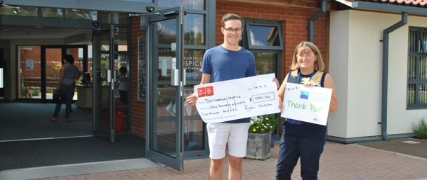 Ryan Hudson holding a cheque and Lynn Lockheart holding a board saying thank you