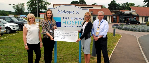 three ladies and a man next to the Hospice sign with a large cheque