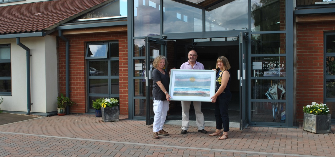 three people holding a painting outside the main doors at the Hospice