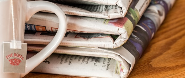 four newspapers with a coffee cup