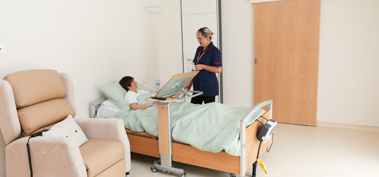 Patient in bed in room with nurse