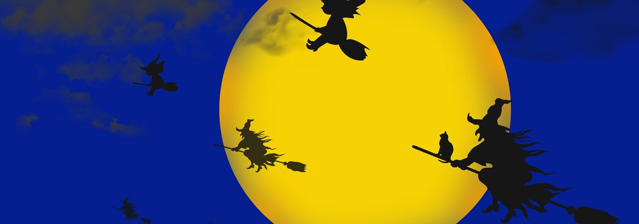 a yellow moon with witches on broomsticks