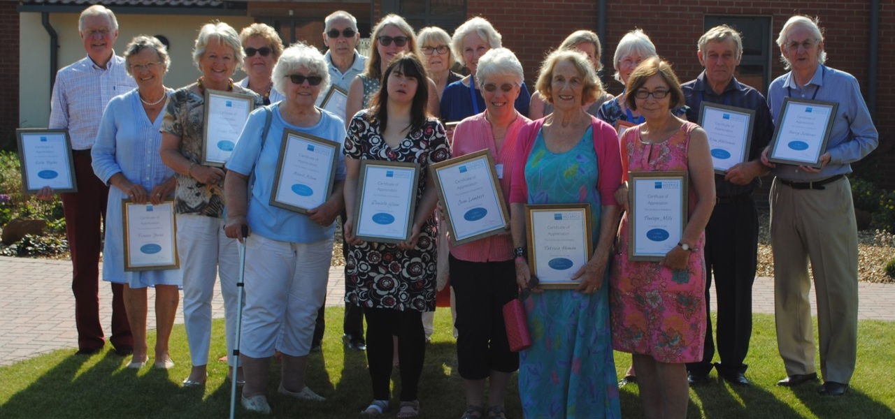 Volunteers holding up their certificates