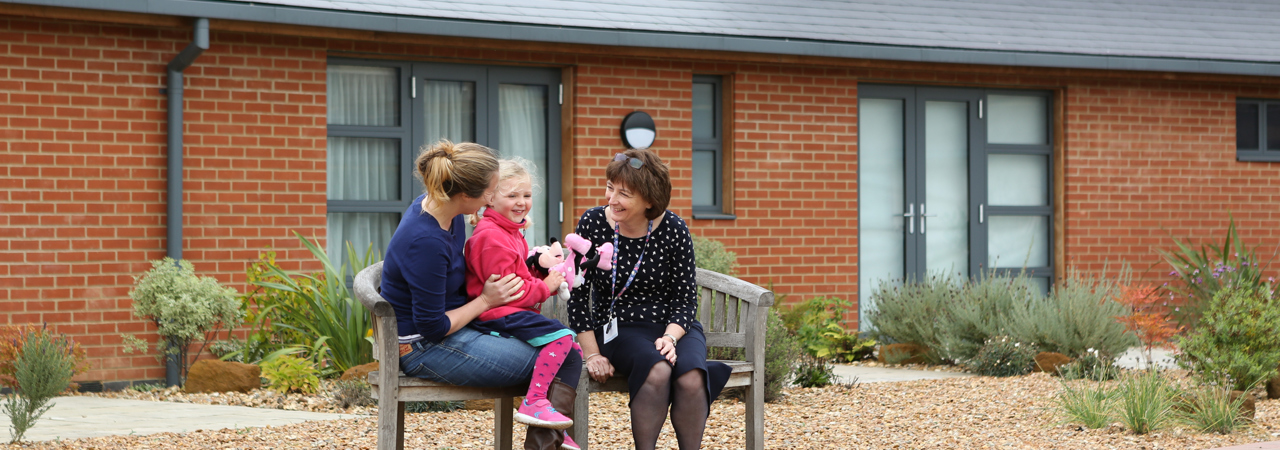 A hospice worker with an adult and child in the Hospice garden