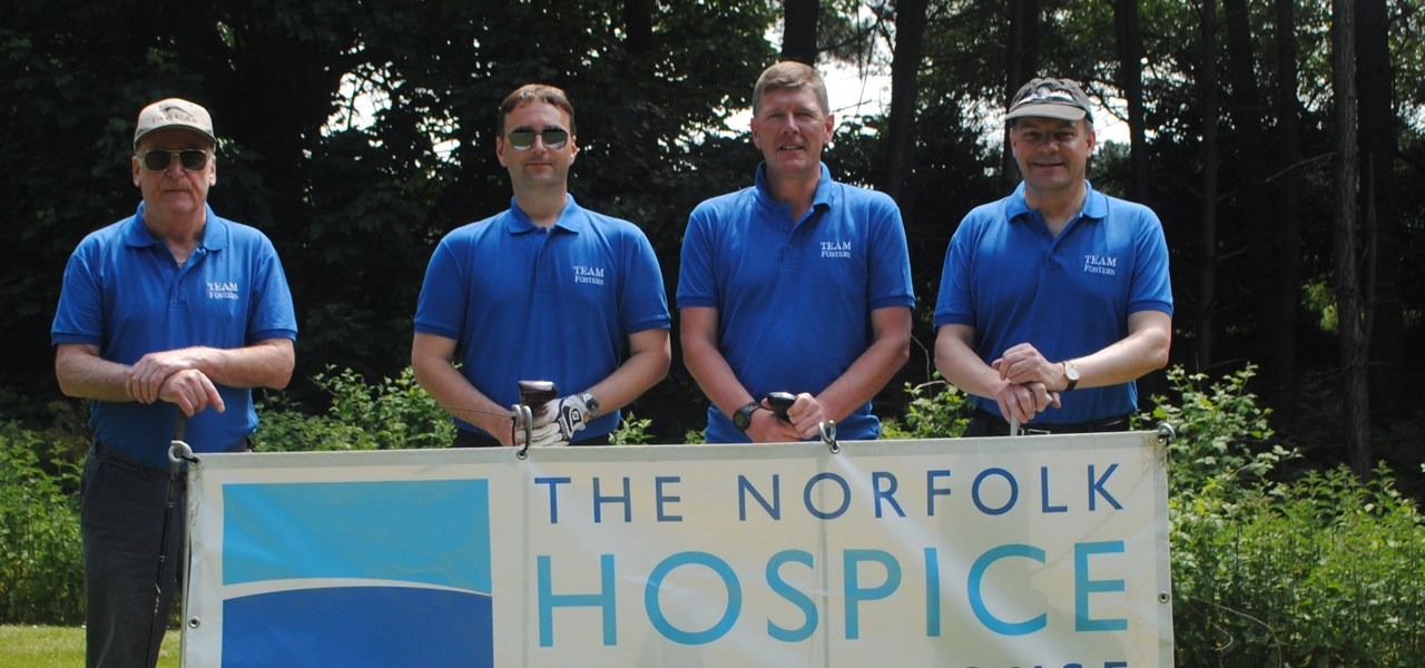 Hospice banner held by group of people in Hospice T shirts
