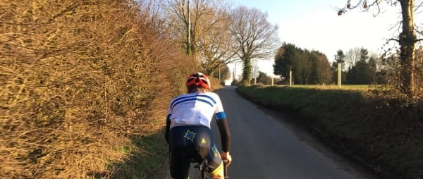 A cyclist on a road bike pictured from behind