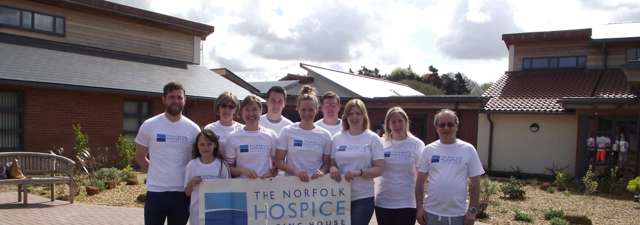 Group of people holding a banner in the Hospice garden