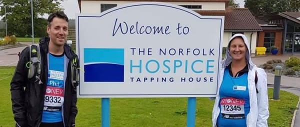 Virtual Marathon runners beside Norfolk Hospice banner 2020