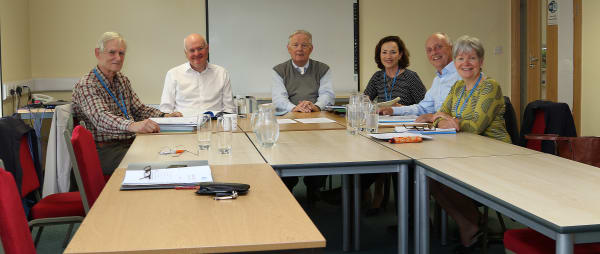 The Trustees seated around the boardroom table