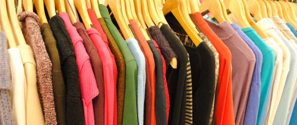 brightly coloured clothes on hangers