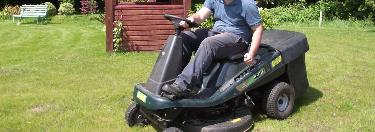 Volunteer on a ride on grass cutting tractor