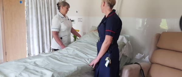 two nurses either side of a ward bed